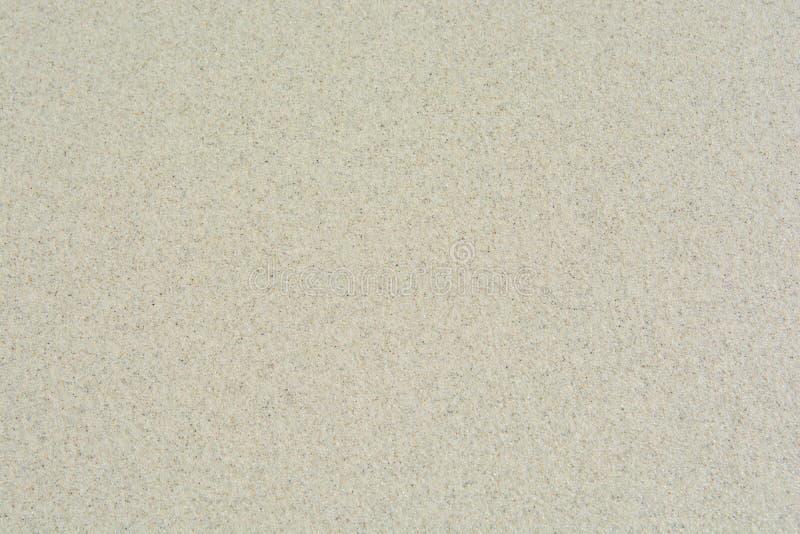 Weißer Sandstrand-Beschaffenheitshintergrund stockfoto