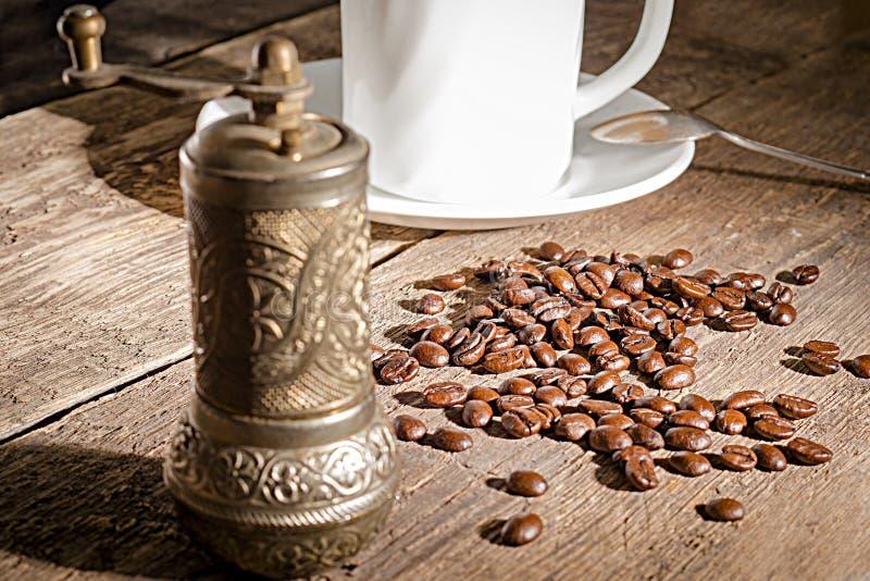 Weißer Schalenkaffee mit Kaffeebohnen, Kaffeemühle und leerem Kreidebrett auf hölzerner Spitzentabelle stockfotos