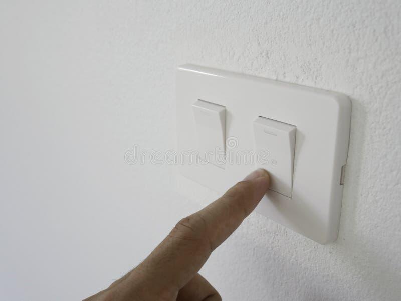 Weißer Schalter der Mannfinger-Presse weg vom Licht auf weißer Wand lizenzfreie stockfotografie