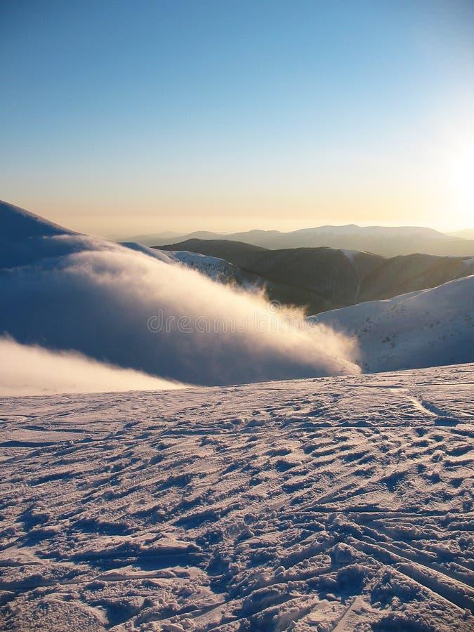 Weißer Schnee umfasste Bergspitzen auf Hoch Nebelflüsse über den Berg Verlassene blaue extreme Winterlandschaft lizenzfreies stockbild