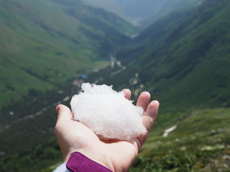 Weißer Schneeball in der Hand auf einem Hintergrund von malerischen Bergen an einem sonnigen Sommertag lizenzfreie stockfotografie