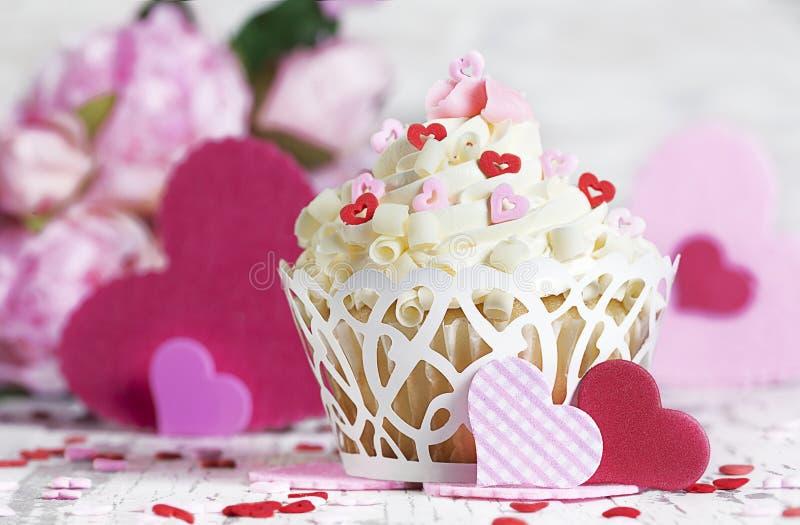 Weißer Schokoladen-kleiner Kuchen mit Herzen und Blumen stockfoto