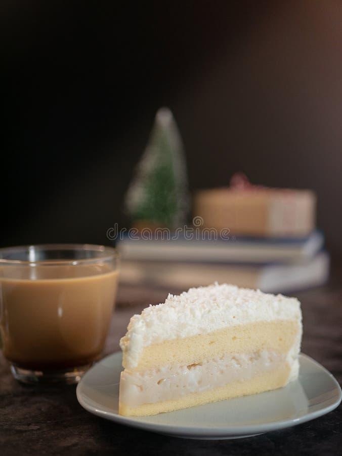Weißer Schokoladenkuchen mit Kokoscremefüllung auf weißer Platte mit einer Tasse Kaffee auf dem Tisch serviert Vertikalbild, zuge lizenzfreies stockfoto