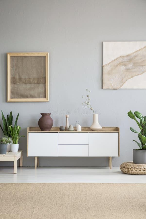 Weißer Schrank zwischen Anlagen im grauen Wohnzimmerinnenraum mit lizenzfreies stockbild