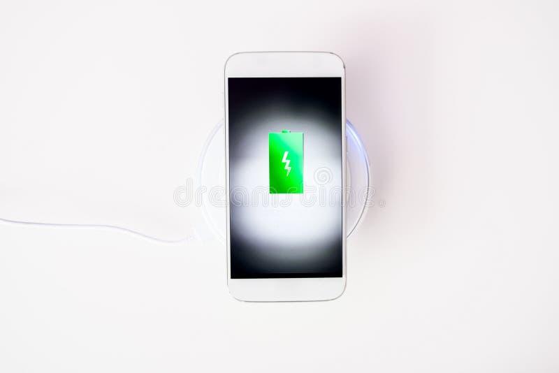 Weißer Smartphone aufgeladen durch drahtloses Ladegerät lizenzfreie stockfotografie