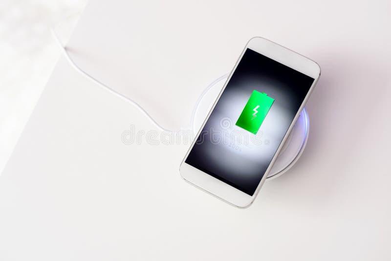 Weißer Smartphone aufgeladen durch drahtloses Ladegerät stockbild