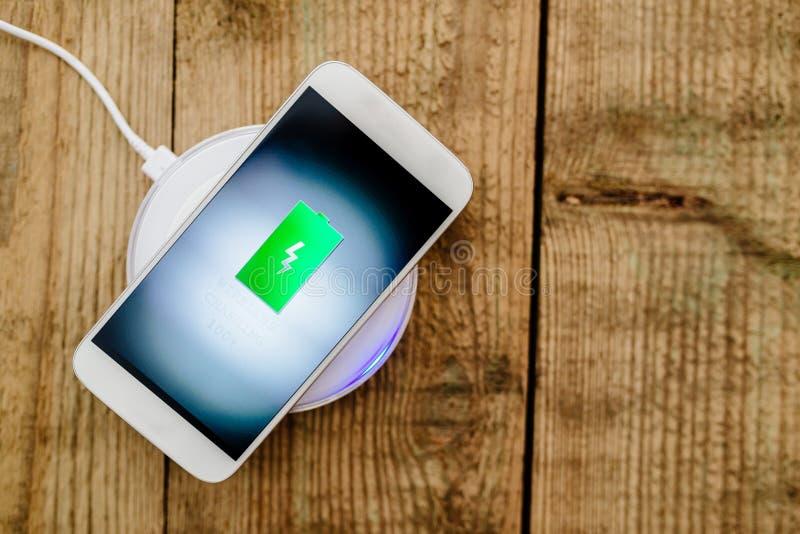 Weißer Smartphone, der auf einer Aufladungsauflage auflädt stockfoto