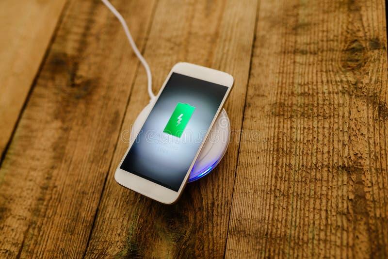 Weißer Smartphone, der auf einer Aufladungsauflage auflädt stockfotos