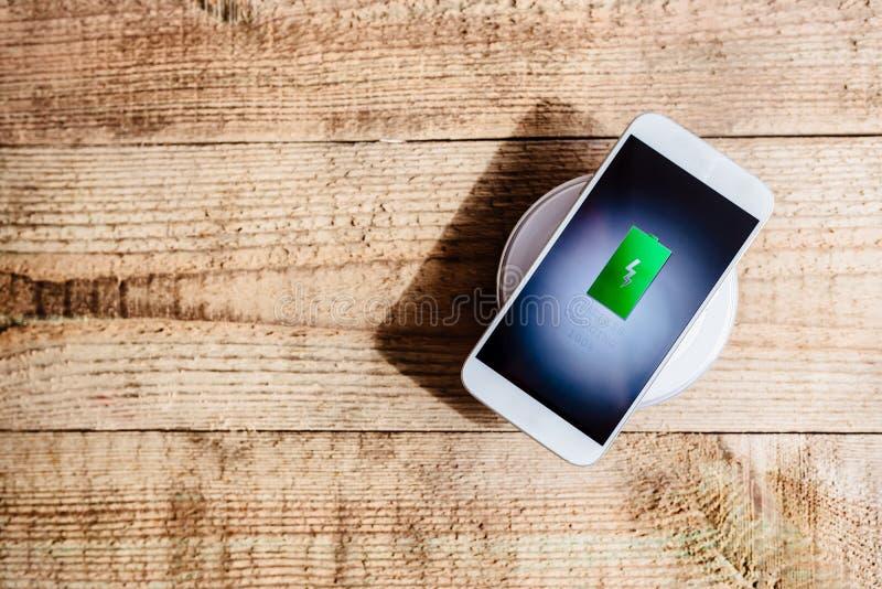 Weißer Smartphone, der auf einer Aufladungsauflage auflädt stockbilder