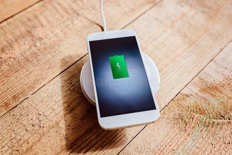 Weißer Smartphone, der auf einer Aufladungsauflage auflädt lizenzfreies stockbild