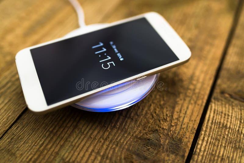 Weißer Smartphone, der auf einer Aufladungsauflage auflädt lizenzfreie stockfotografie