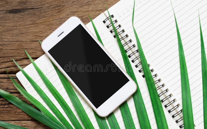 Weißer Smartphone mit schwarzem leerem Modellschirm mit grünen Palmblättern und offenem Notizbuch auf der hölzernen Schreibtischt lizenzfreie stockfotografie