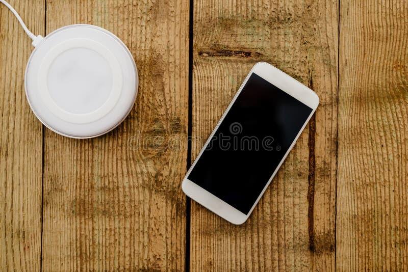Weißer Smartphone und Aufladungsauflage stockfotografie