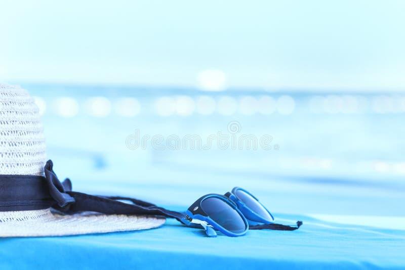 Weißer Sommerhut mit Sonnenbrille an der Küste stockfoto