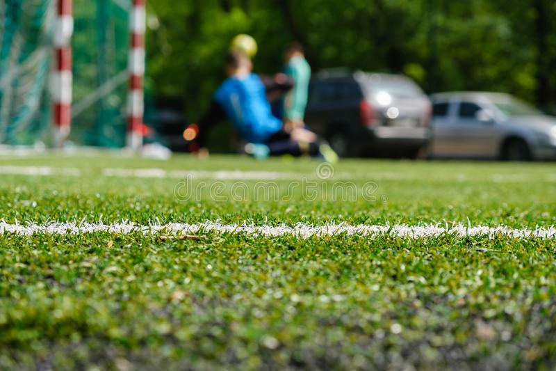 Weißer Streifen auf künstlichem grünem Fußballfußballplatz von der Seitenansicht lizenzfreie stockfotos