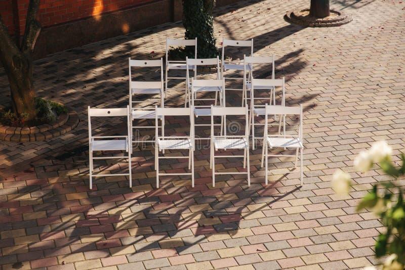 Weißer Stuhl auf Hochzeitszeremonie Sommerhochzeitsdekoration draußen stockfotos