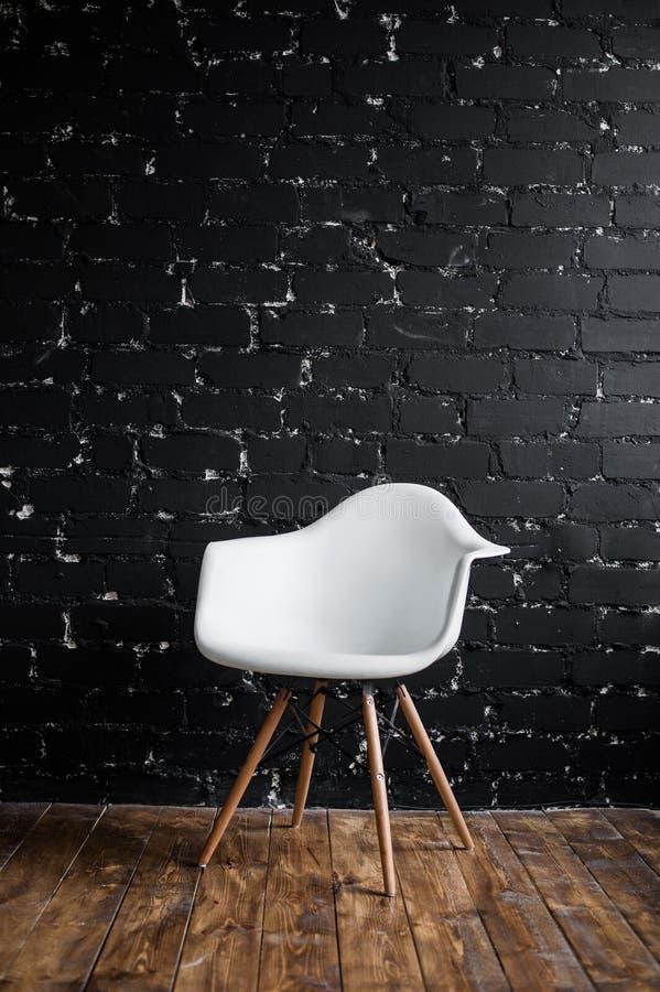 Weißer Stuhl, der im Raum auf braunem Bretterboden über schwarzer Backsteinmauer steht stockfotos
