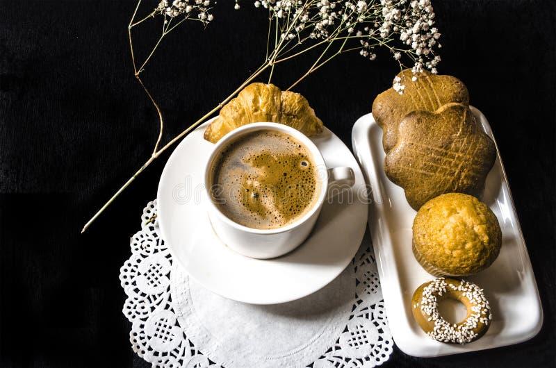 Weißer Tasse Kaffee, Bäckereiprodukt auf weißer Platte und Zweig lizenzfreie stockfotos