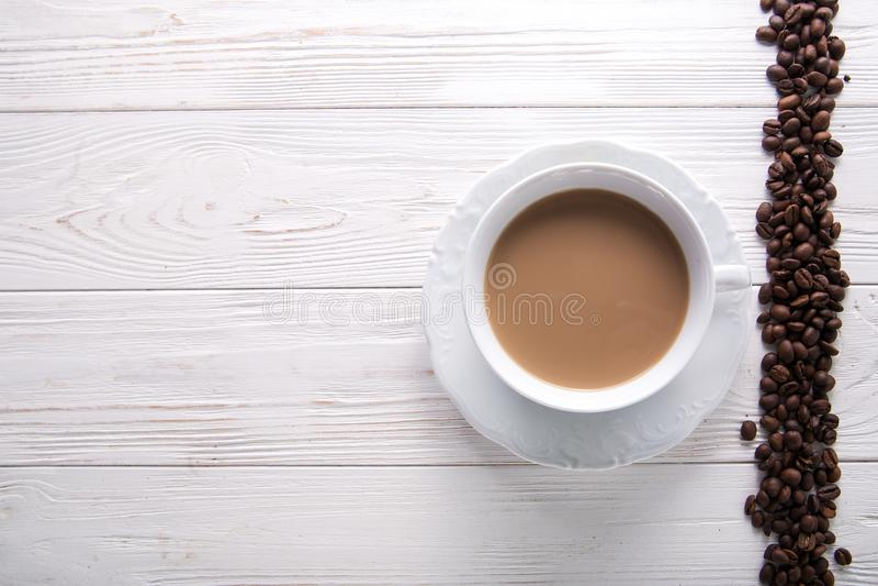 Weißer Tasse Kaffee mit Milch oder Tee mit Milch auf dem weißen hölzernen Hintergrund verziert mit Kaffeebohnen stockfoto