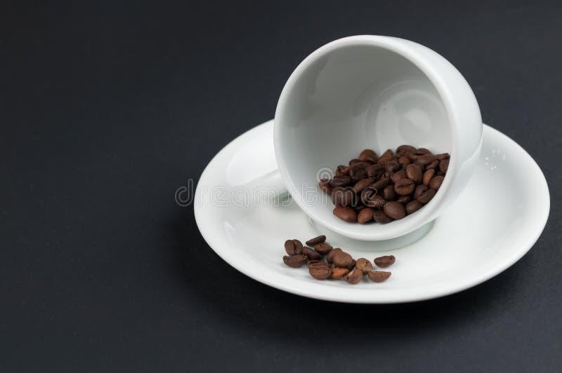 Weißer Tasse Kaffee und Kaffeebohnen lokalisiert auf schwarzem Hintergrund stockfotografie