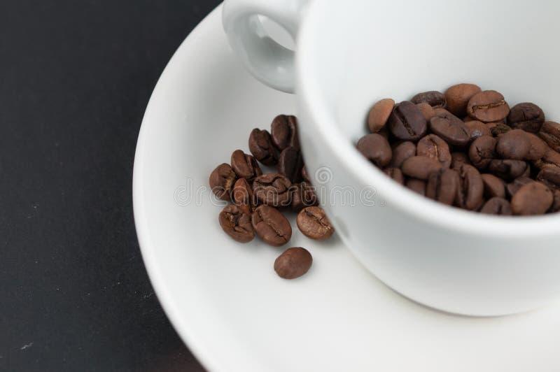 Weißer Tasse Kaffee und Kaffeebohnen lokalisiert auf schwarzem Hintergrund lizenzfreies stockfoto