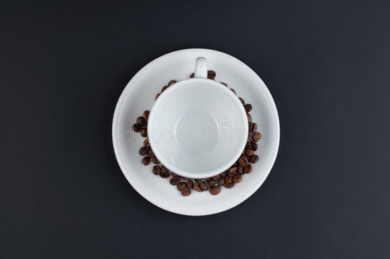 Weißer Tasse Kaffee und Kaffeebohnen lokalisiert auf schwarzem Hintergrund stockfoto