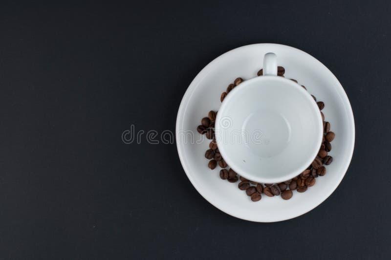 Weißer Tasse Kaffee und Kaffeebohnen lokalisiert auf schwarzem Hintergrund stockfotos