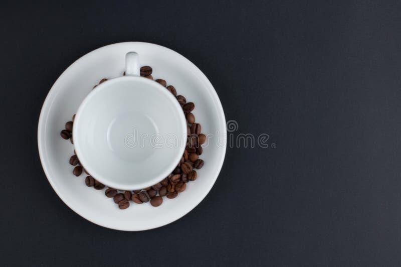 Weißer Tasse Kaffee und Kaffeebohnen lokalisiert auf schwarzem Hintergrund lizenzfreie stockfotos