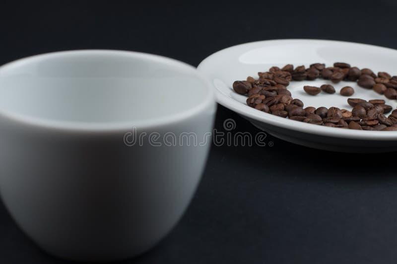 Weißer Tasse Kaffee und Kaffeebohnen lokalisiert auf schwarzem Hintergrund stockbild