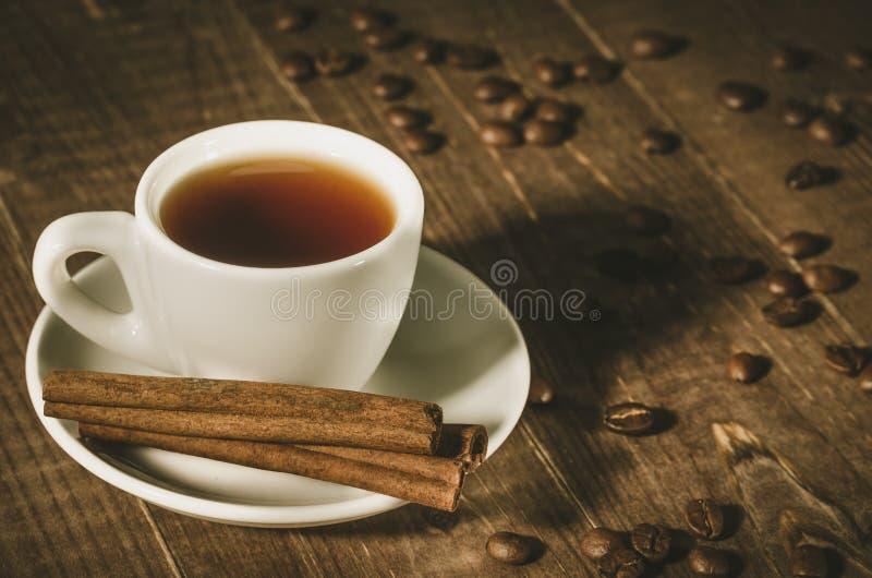 Weißer Tasse Kaffee, Zimtstangen und Kaffeebohnen/weißes c lizenzfreie stockfotografie
