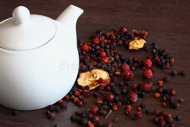 Weißer Teetopf und süße Trockenfrüchte und Beeren auf dunkelbraunem Holztisch Natürliches rustikales Frühstück lizenzfreies stockbild