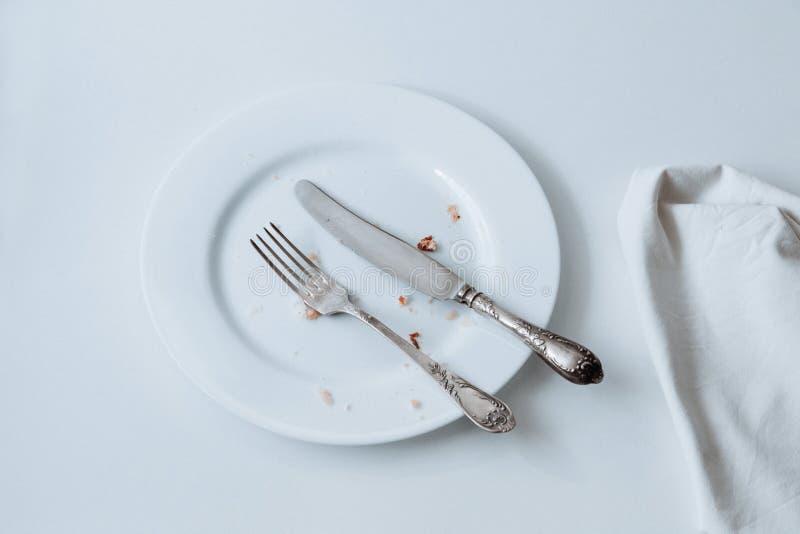 Weißer Teller mit Gabel, Messer und auf weißem Untergrund zerknittert stockbilder