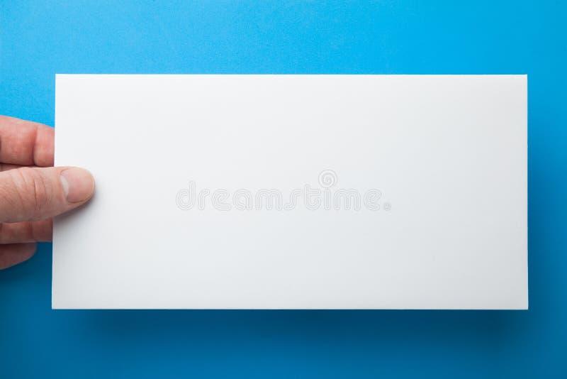 Weißer Umschlag in der Hand auf einem blauen Hintergrund stockbild
