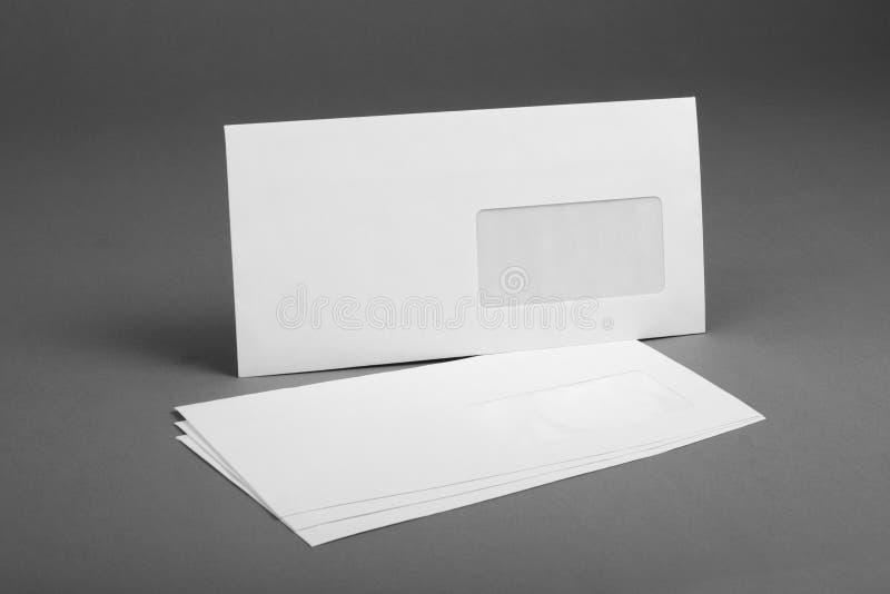 Weißer Umschlag mit Adreßfenster auf grauem Hintergrund lizenzfreies stockfoto