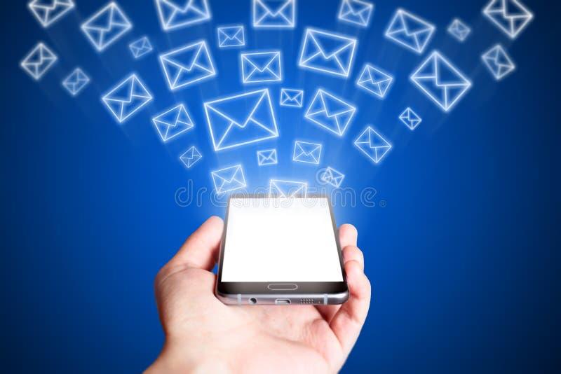 Weißer Umschlag mit @ am Symbol auf einem Blatt nach innen Handy auf blauem Hintergrund stockbilder