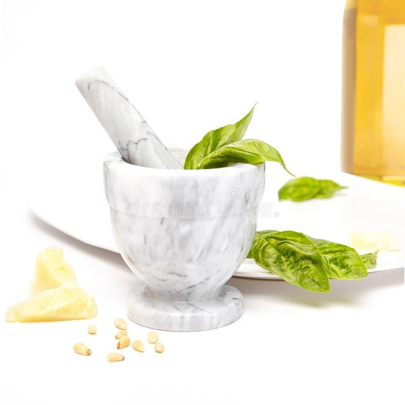 Weißer und grauer Marmormörser und Stampfe mit Pestobestandteilen, Olivenöl, Basilikum, Kiefernnüssen und Parmesankäseparmesankäs lizenzfreie stockbilder