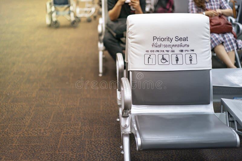 Weißer und grauer piority Sitz nahe Zugang im Flughafen, mit Unschärfepassagieren hinten Thailändische und chinesische Sprachdurc lizenzfreie stockbilder