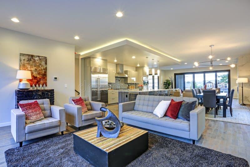 Weißer und grauer Wohnzimmerinnenraum mit offenem Grundriss stockfotografie