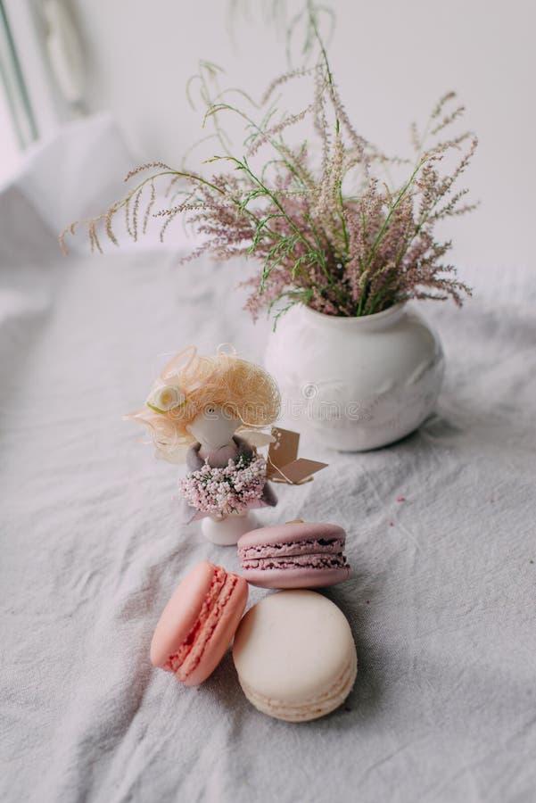 Weißer Vase mit einem Blumenstrauß und einem Kuchen Makkaroni stockfotografie