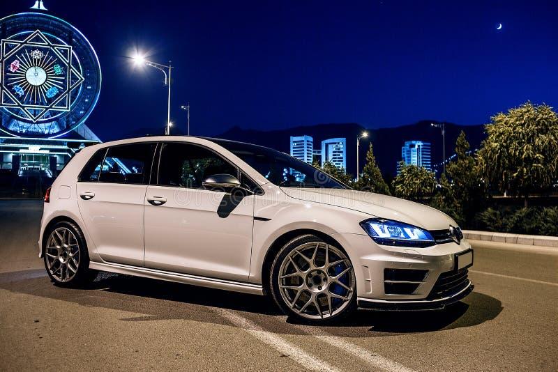 Weißer VW spielen am Abend nahe bei dem Riesenrad Golf Ansicht von der Ecke lizenzfreie stockbilder