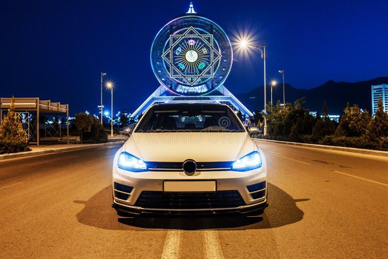 Weißer VW spielen am Abend nahe bei dem Riesenrad Golf Ansicht von der Front lizenzfreie stockbilder