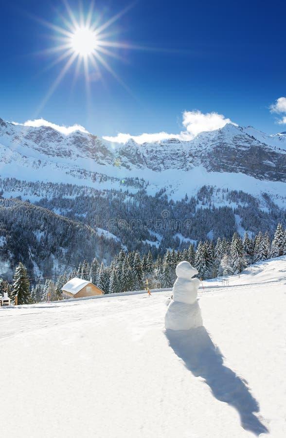 Weißer Wald, blauer Himmel, Sonne und Schneemann in den Schweizer Alpen während eines schönen sonnigen Tages, Klewenalp-Skiort stockfotos