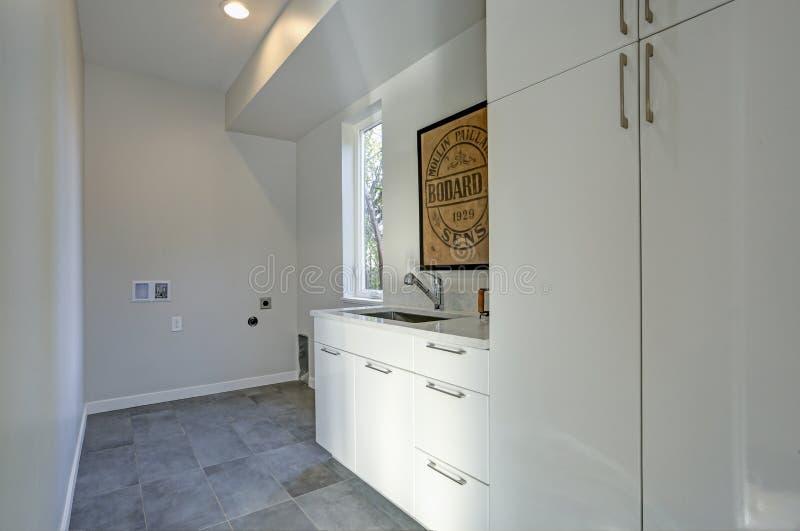 Weißer Waschkücheinnenraum mit Kabinetten und grauem Fliesenboden lizenzfreie stockbilder