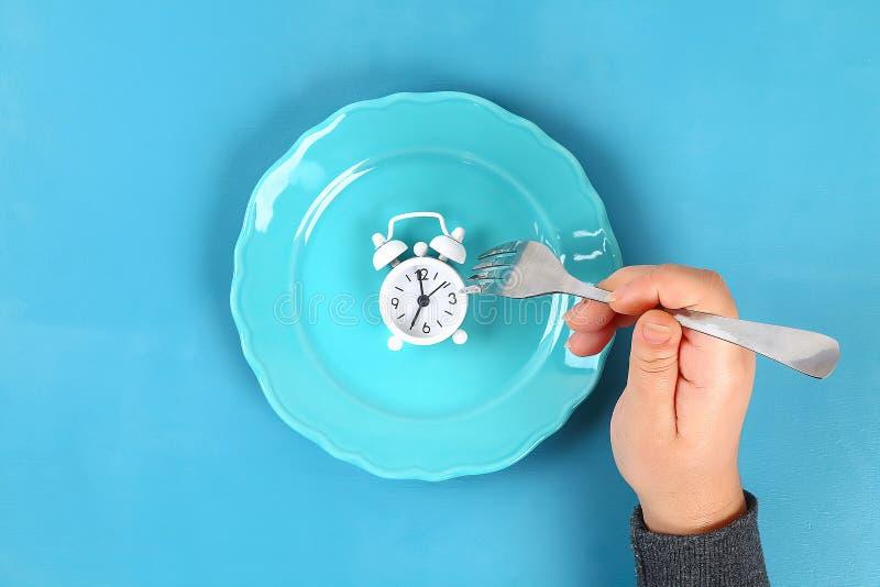 Weißer Wecker in der blauen leeren Platte Zeit, Gewicht zu verlieren, Steuerung oder Zeit essend, Konzept zu nähren stockbild