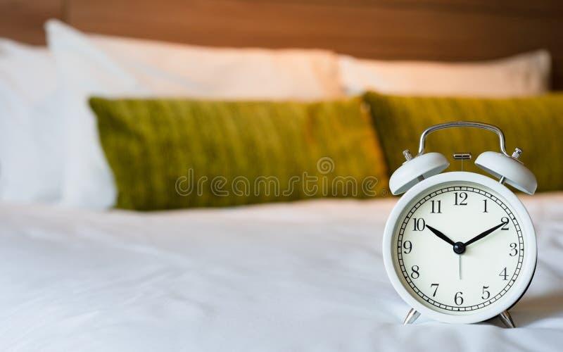 Weißer Wecker der Weinlese auf Schlafzimmer Einkaufszeithintergrundkonzept mit Kopienraum lizenzfreie stockbilder