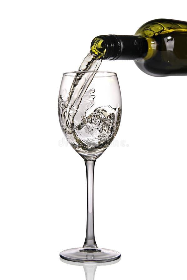 Weißer Wein, der in Glas gegossen wird lizenzfreie stockbilder