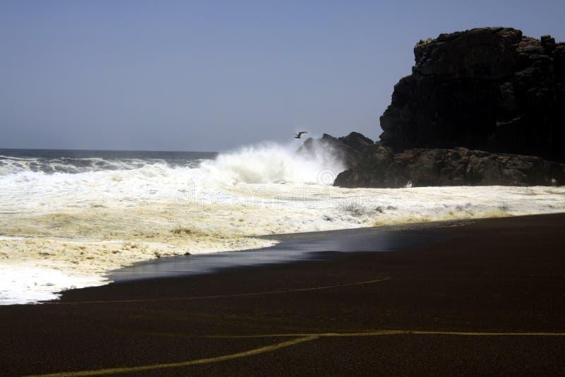 Weißer Wellenbrecherschaumschlag auf einsamem schwarzem Lavasandstrand an der pazifischen Küstenlinie - Cobquecura Piedra De La L stockbild