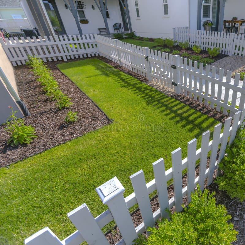 Weißer Zaun um ein sonnenbeschienes landschaftlich gestaltetes Yard lizenzfreies stockfoto