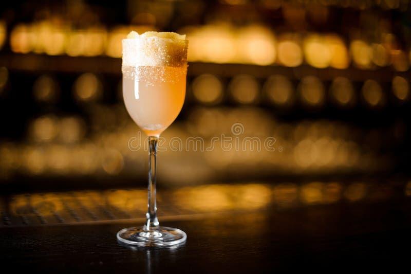 Weißes achoholic Getränk mit Abschaum im Cocktailglas verziert mit braunem Zucker und orange Eifer lizenzfreie stockbilder