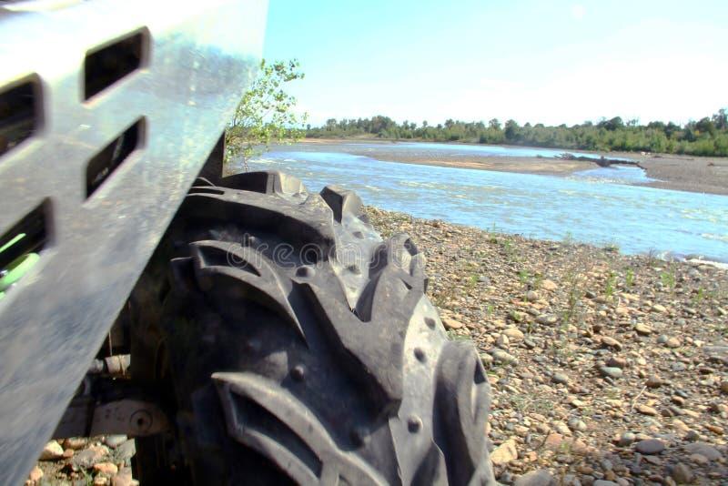Weißes ATV steht an einem sonnigen Tag durch den Fluss Ansicht des Rades lizenzfreie stockfotos